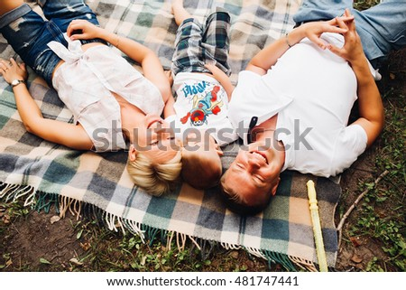 Happy family. Father, mother and son are laughing, look sverse, dressed in the same style. White t-shirts and shorts. Family idyll, the concept of happiness, family