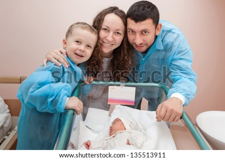 Happy family; father, mother, and son bending over their newborn daughter in the maternity hospital - stock photo