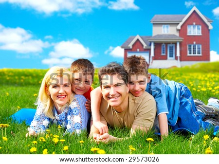 Happy family. Father, mother and sons on the green grass - stock photo