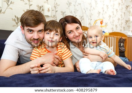 Happy family. father, mother and two children relaxing on sofa at home. Family looking at the camera on their bed - stock photo