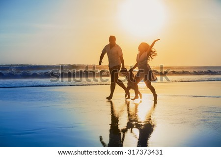 Happy family - father, mother, baby son hold hands and run with fun along edge of sunset sea on black sand beach. Active parents and people outdoor activity on tropical summer vacations with children - stock photo