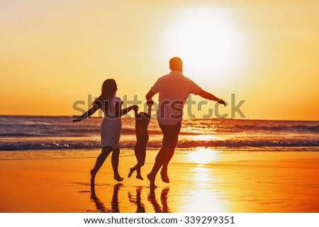 Happy family - father, mother, baby son hold hands and run with fun along edge of sunset sea on black sand beach. Active parents and people outdoor activity on tropical summer vacations with children. - stock photo