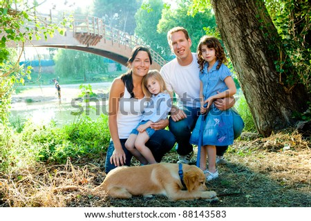 Happy family father mother kids and dog outdoor river park - stock photo