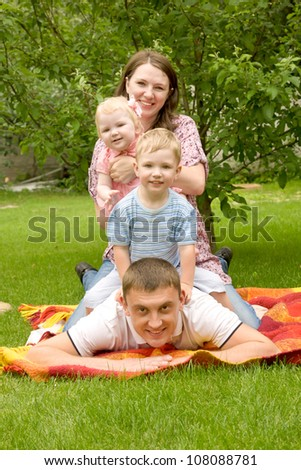Happy family - father, mother, son, baby daughter on the grassy lawn. Family members sit on each other, forming a tower - stock photo