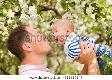 Happy family. Father throws up child in the blooming apple trees, on sunny day in the park. Positive human emotions, feelings. Cherry and apple blossom. Spring time. outdoors. Father and baby son.