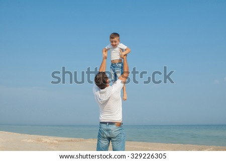 Happy family. Father throws up child in the sky, on sunny day the beach. Positive human emotions, feelings. - stock photo