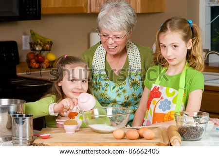 Happy Family featuring a friendly Grandma baking cookies in a home kitchen with her two Grandchildren. - stock photo
