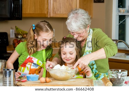 Happy Family featuring a friendly Grandma baking cookies in a home kitchen with her two Grandchildren.