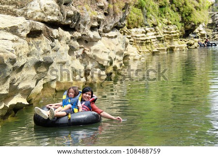 Happy family floating on inflatable tube in river during vacation - stock photo