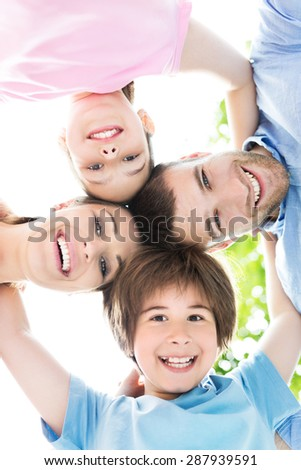 Happy family forming a huddle - stock photo