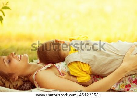 Happy family, friends forever concept. Profile portrait of smiling mother and little son lying together. Mom laughing. Sunny summer day. Close up. Copy-space. Outdoor shot