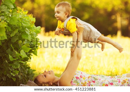 Happy family, friends forever concept. Profile portrait of smiling mother and little son playing together. Mom lifting baby up in air. Sunny summer day. Outdoor shot - stock photo