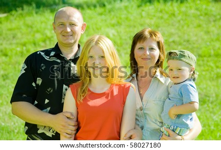 Happy family from four posing against nature - stock photo