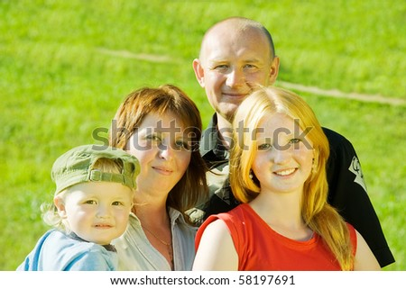 Happy family  from four posing on grass against nature - stock photo