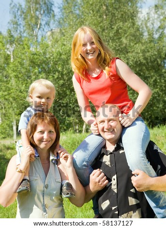 Happy family from four stands on grass against nature - stock photo