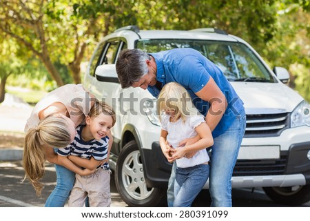 Happy family getting ready for road trip on a sunny day - stock photo