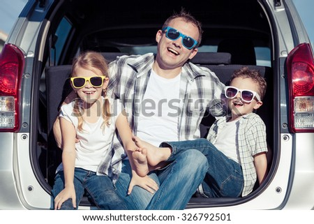 Happy family getting ready for road trip on a sunny day.  Concept of friendly family. - stock photo