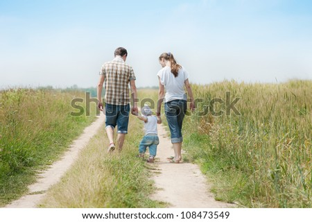Happy family go in the meadow - stock photo