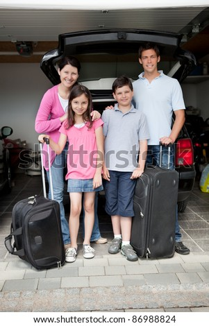 Happy family going on holiday standing by their car boot with their luggage