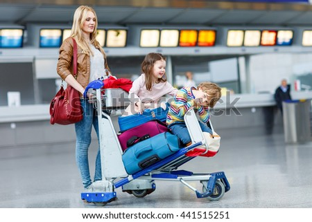 Happy family going on vacation. Mother and two little kids on international airport, sitting on suitcases. Brother and sister having fun and wating for flight - stock photo