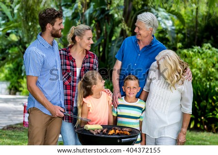 Happy family grilling food in barbeque at yard - stock photo