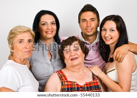 Happy family group  with grandma,mother and three children standing together in embrace and smiling - stock photo