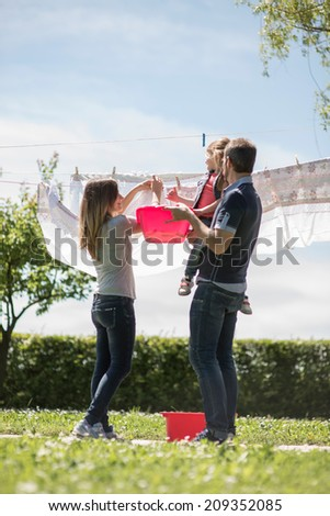 Happy family hanging up laundry - stock photo