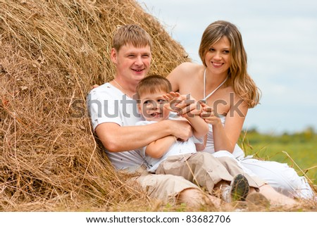 Happy family has fun in haystack together - stock photo