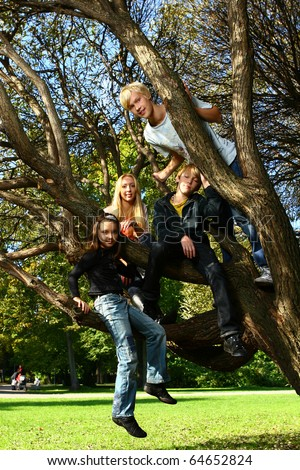 Happy family have fun and stroll in park have fun on a tree - stock photo