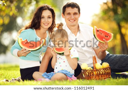 Happy family having a picnic in the green garden - stock photo