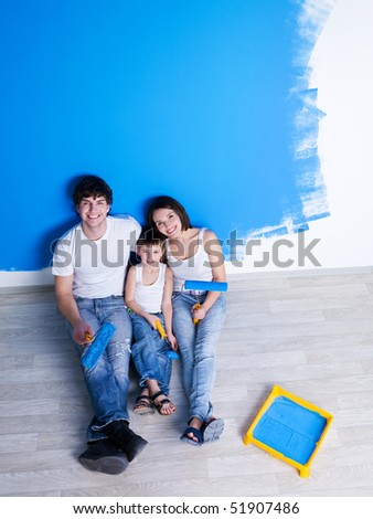 Happy family having a rest after painting the wall - high angle - stock photo