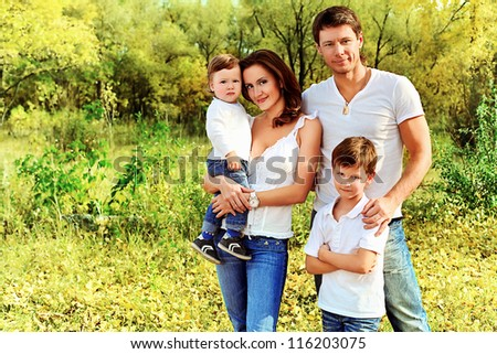 Happy family having a rest outdoor in the autumn park. - stock photo