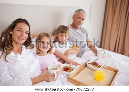 Happy family having breakfast in a bedroom while looking at the camera