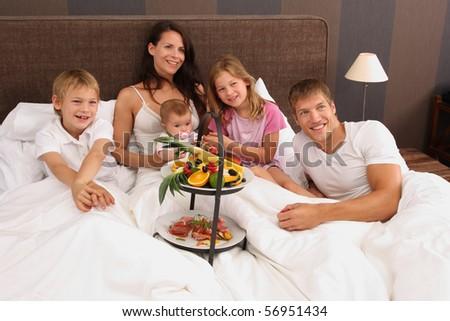 Happy family having breakfast in bed - stock photo