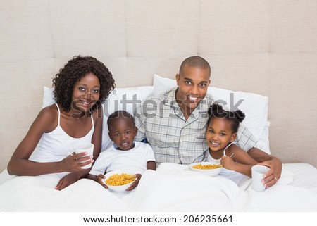 Happy family having breakfast in bed together in the morning at home in the bedroom