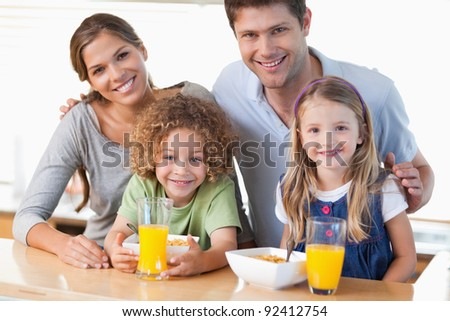 Happy family having breakfast in their kitchen - stock photo