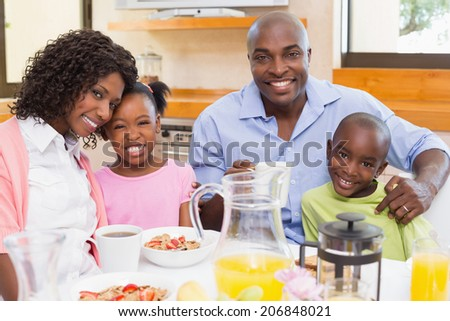 Happy family having breakfast together in the morning at home in the kitchen - stock photo