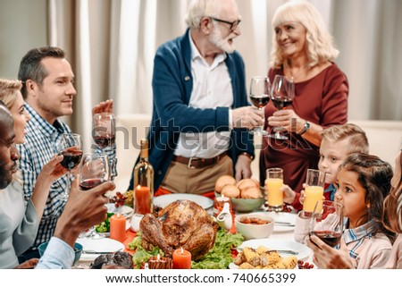 Happy Family Having Christmas Dinner While Grandparents Clinking Glasses