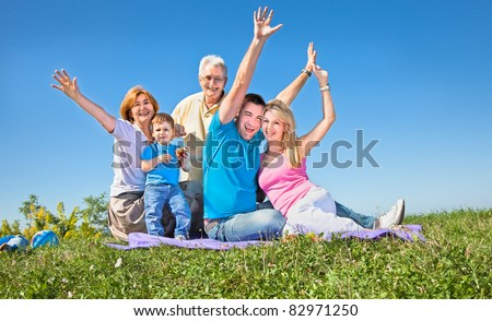 Happy family having fan in park on sunny day under the clear blue sky - stock photo