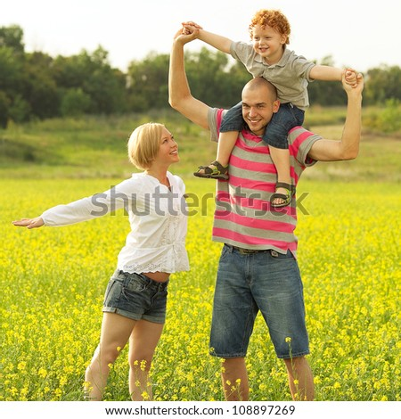 happy family having fun and doing plane figure in the field with yellow flowers. outdoor shot - stock photo