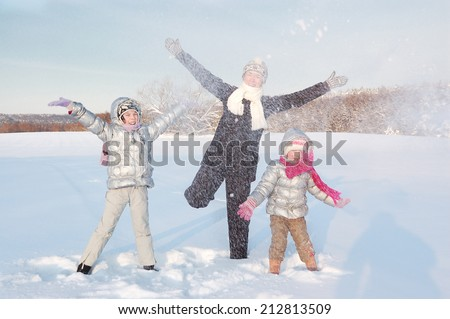 Happy family having fun and playing with snow outdoors  - stock photo