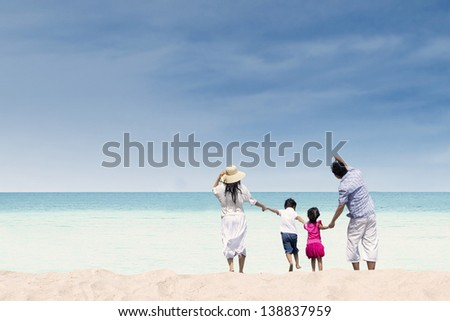 Happy family having fun at beach during summer day