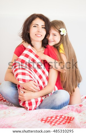 Happy family having fun at home. Mother and daughter in bedroom