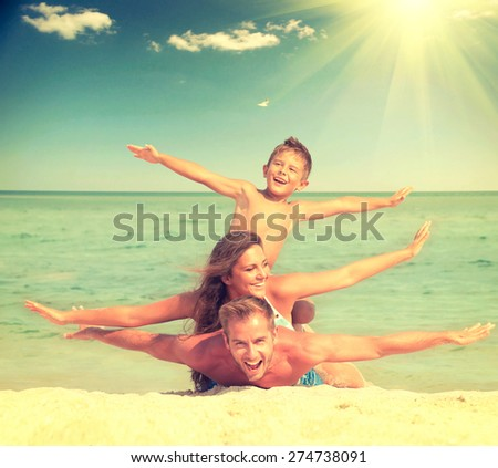 Happy Family Having Fun at the Beach. Joyful Family. Vacation and Travel concept. Summer Holidays. Parents with Son enjoying a holiday at the sea. Toned photo - stock photo