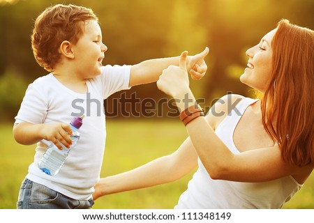 happy family having fun. baby boy with brown curly hair and  his mother with ginger hair showing thumb up each other. outdoor shot - stock photo