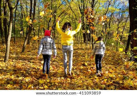 Happy family having fun in autumn forest playing and throwing leaves