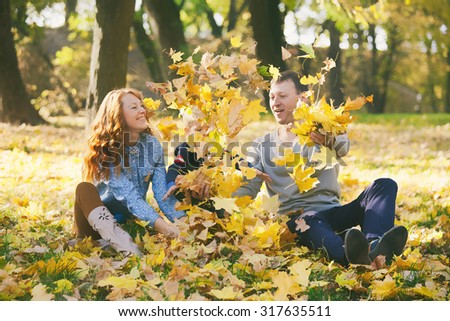 Happy family having fun in autumn urban park. Daddy, mommy and little son playing together outside with autumn lush foliage on sunny day. family spending time together outside. - stock photo
