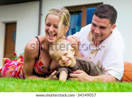 Happy family having fun in front of their house - stock photo
