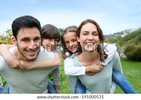 Happy family having fun in home garden - stock photo