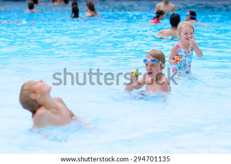 Happy family having fun in recreation swimming pool. Children enjoying day in waterpark during active summer holidays. Kids laughing and playing with waterguns. Selective focus on little girl. - stock photo